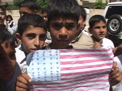 An Iraqi boy holds up a drawing of the American flag in... Stock Video Footage