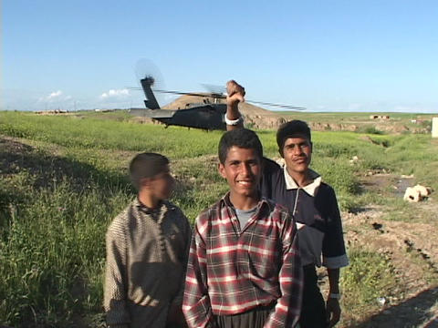 Iraqi boys pose and give peace signs in front of a Blackhawk helicopter Footage