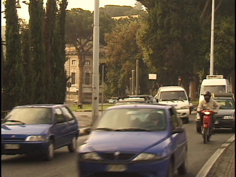 Traffic travels down a street in Rome Stock Video Footage