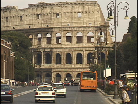 Traffic travels down a street in front of the Coliseum Stock Video Footage