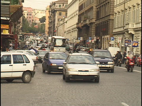 Traffic travels up a crowded street in Rome Stock Video Footage
