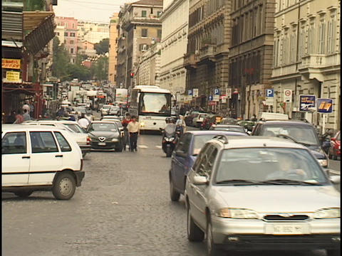Traffic travels up a crowded street in Rome Footage