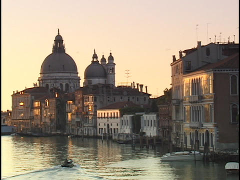 A small boat motors through the Grand Canal and past the Santa Maria del Salute in Venice, Italy Footage