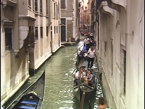 Tourists ride gondolas through a narrow waterway on the... Stock Video Footage