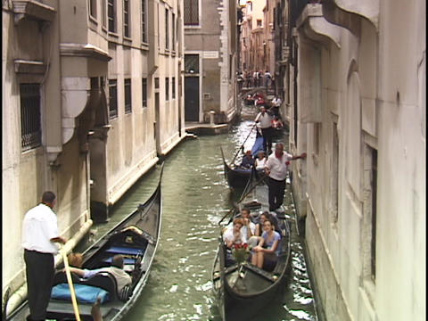 Tourists ride gondolas through a narrow waterway on the Grand Canal in Venice, Italy Footage