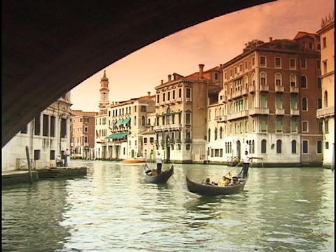 Tourists ride gondolas under the Rialto Bridge on the... Stock Video Footage