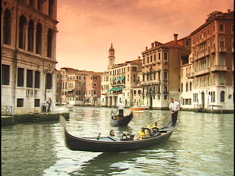 Tourists ride gondolas under the Rialto Bridge on the Grand Canal in Venice, Italy Footage