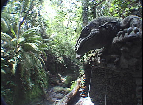 Small streams of water fall beneath a giant stone lizard... Stock Video Footage