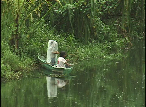 young boys fish from a tiny boat on the verdant banks of a jungle river Footage