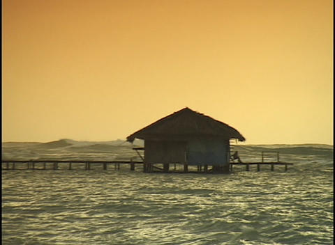 A woman sits and watches waves crashing around her small hut Stock Video Footage