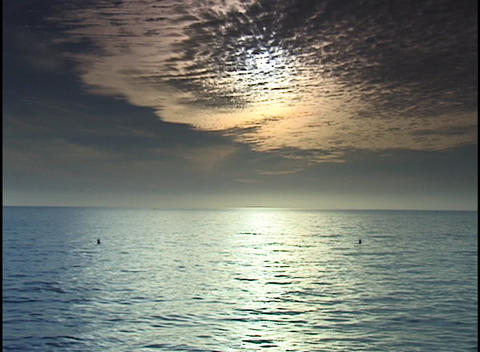 The sun shines through thin layers of clouds and shimmers across the ocean Footage