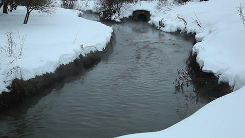 Black stream between snowy banks, dark contaminated water flow over waste land Footage