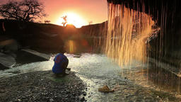 Child watching a waterfall and tossing a rock Footage