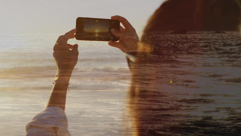 Woman taking a picture at the beach during sunset Animation