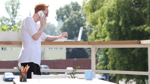 Young Man Talking on Phone, Standing in Balcony Outdoor Footage
