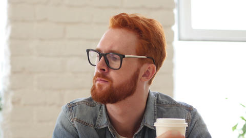 Man with Beard and Red Hairs Drinking Coffee, Tea in Office, Portrait Footage