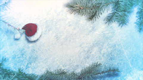 Animated closeup Christmas cap and green tree branches on shiny ice background Animation