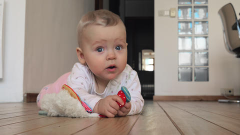Sweet blue-eyed baby girl with toy on the floor at home Acción en vivo
