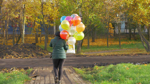 A slowmotion of a woman walking with balloons on a beautiful autumn day Acción en vivo