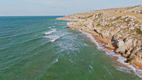 Aerial shot from the drone Flight out from the coast with rocks and tide with Live Action
