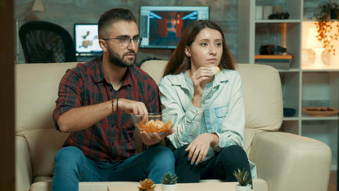 Concentrated caucasian young couple while watching tv Live Action