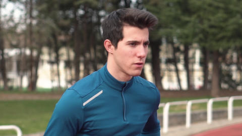 Fitness young man running outdoor at sport stadium. Male runner running outside Live Action
