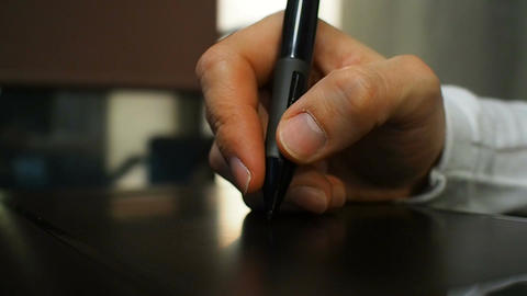 Tablet 19. Close up of the hand of a graphic designer holding an electronic styl Footage