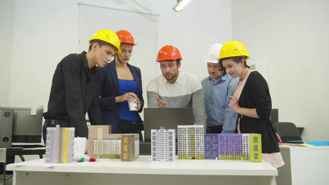 Architects in helmets look at computer and discuss a project and models of Live Action