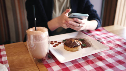 Girl edits and sends a photo of her dish, dessert on a smartphone to the social Live Action