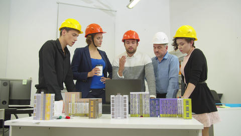 People in helmets discuss a project and models of houses Live Action