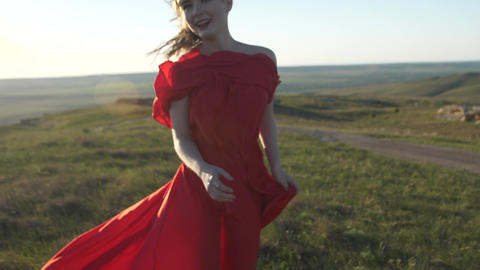 Blurred image of a woman in a red dress running across the field and laughing Live Action
