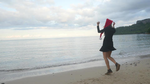 Funny woman in Santa hat funny dancing near the sea Live Action