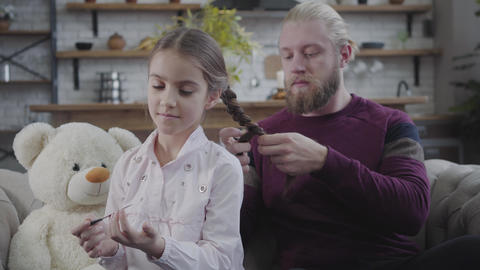 Portrait of little brunette Caucasian girl in white shirt filing nails as father Live Action