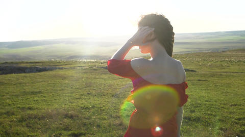 A young woman in a red dress stands in the background of a light filled field of GIF