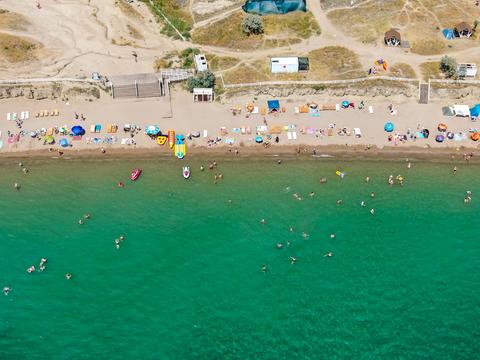 Bird's-eye view. Sea beach people swimming sunbathing relaxing. Human footprints Photo