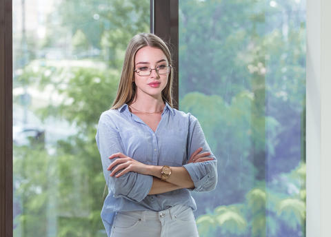 Thoughtful young lady with glasses in blue shirt is thinking about and dreaming Photo