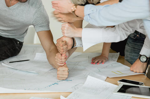 Corporate training employees build a pyramid of fists on the table On the table Photo