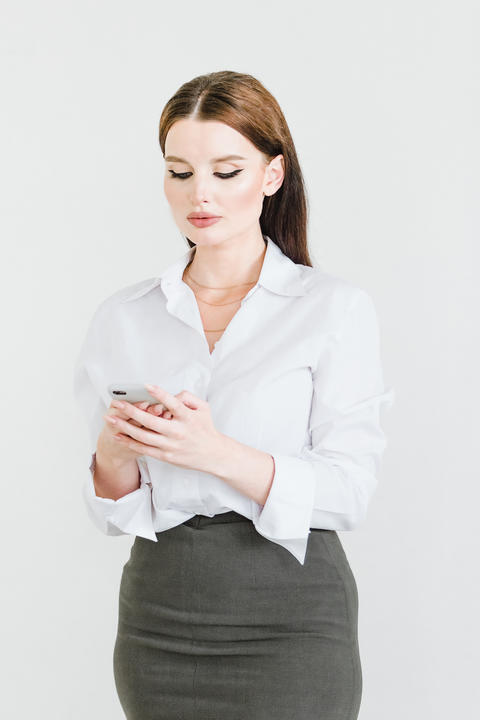 A business woman in a skirt and blouse uses a smartphone for communication and Photo