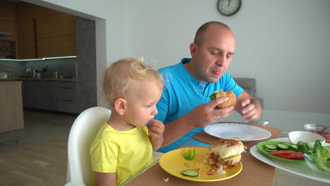 Boy and his father eating hamburger fast food at home. unhealthy lifestyle Live Action