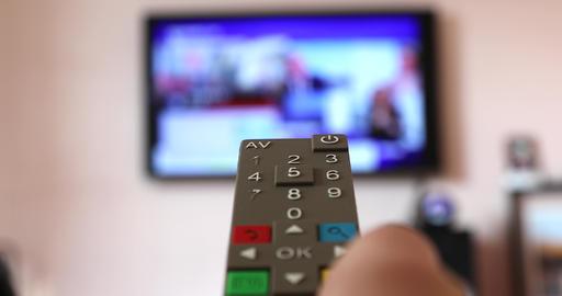 Man Hand Holding The TV Remote Control Of The Smart TV Acción en vivo
