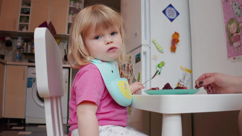 Little two years old blond blue-eyed girl having her dining, 4K shot Live Action