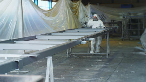 protected employee uses sprayer to paint carcass in workshop Live Action