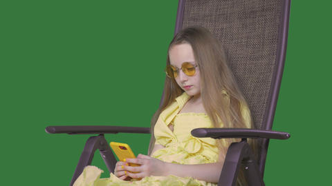 Young girl in yellow dress sitting in beach chair and looking mobile phone. Girl Live Action