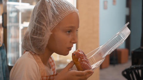 Teenager girl in disposable hat and kitchen apron eating donut. Cook girl eating Live Action