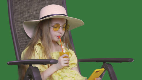 Young girl drinking orange juice and looking smartphone in summer day. Girl Live Action