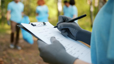 Close-up of female hand writing volunteer report in forest during clean-up work Live Action