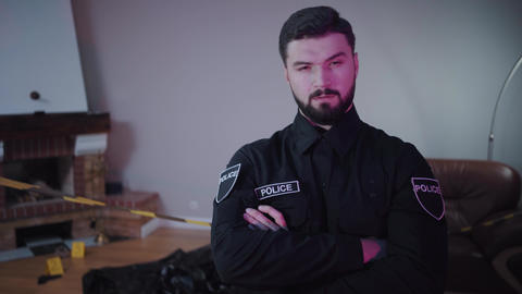 Portrait of confident Caucasian police officer with brown eyes and black hair Live Action