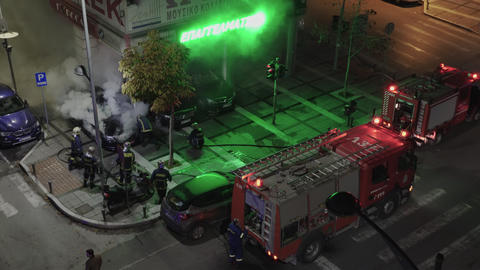 Greek firefighters during fire at luxury car showroom in Thessaloniki, Greece Live Action