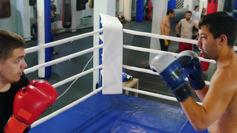 Boxing indoors - two men having a training fight on the boxing ring - attack and Live Action