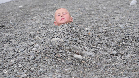 Beach summer vacation. Boy gets out from under the pebbles smiles and shows the Live Action
